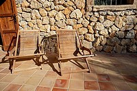 Two wooden deckchairs on tiled patio, stone wall in background