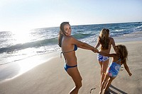 Two girls 5-12 wearing swimwear, pulling mother along sandy beach, woman looking over shoulder, smiling, rear view, sunlight shimmering on sea tilt