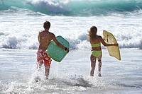 Two teenage 13-15 bodysurfers running into surf, carrying bodyboards, side by side, rear view