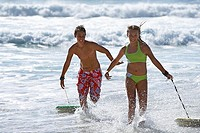 Teenage boy and girl 13-15 exiting surf, pulling bodyboards over water, side by side, smiling