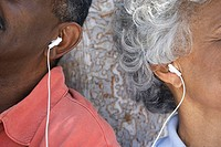 Senior couple listening to MP3 player, sharing earbud headphones, close-up, side by side
