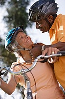 Active senior couple preparing to cycle in park, man adjusting woman's cycling helmet strap, smiling, close-up, low angle view tilt