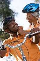 Active senior couple preparing to cycle in park, woman adjusting man's cycling helmet strap, smiling, close-up, low angle view tilt