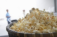 Bowl of popcorn, close-up, people in background, focus on foreground