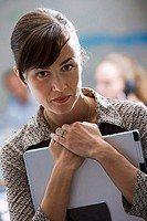 Businesswoman carrying laptop, close-up, front view, portrait, focus on foreground
