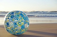 Large blue beach ball on sandy beach, sea in background