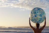 Man standing on beach at sunset, holding beach ball above head, looking at horizon over sea