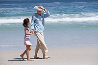 Mother and daughter 6-8 walking on beach, holding hands, woman holding sun hat in breeze, smiling