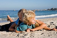 Boy 4-6 and girl 7-9 playing on sandy beach, smiling, side view