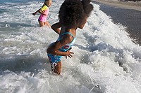 Two girls 6-10 playing in surf at beach, side view