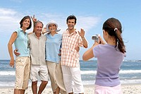 Girl 7-9 photographing three generation family on beach, posing and smiling, sea in background
