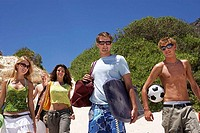 Teenagers 17-19 standing on beach, carrying bodyboard, soccer ball and bags, smiling, portrait