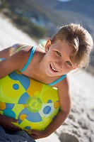 Girl 5-7 lying on green beach ball on sandy beach, smiling, close-up, portrait tilt