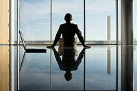 Reflection of businessman sitting on floor, looking through window, rear view, surface level