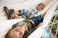 Boy 6-8 and girl 7-9 lying in hammock, smiling, portrait tilt