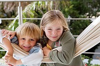 Blonde boy 6-8 and girl 7-9 leaning on hammock, smiling, close-up, portrait