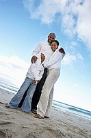 Two generation family in white clothing embracing on beach, smiling, portrait, low angle view tilt
