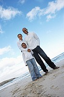 Two generation family in white clothing standing on beach, smiling, portrait, low angle view tilt