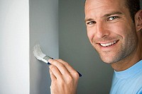 Man decorating at home, painting wall with paintbrush, smiling, close-up, side view, portrait