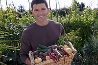 Man standing in garden holding basket of fresh vegetables, smiling, portrait
