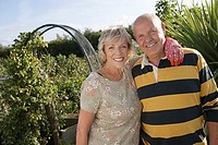 Senior couple standing in garden with arm around each other, smiling, portrait tilt