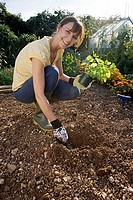 Woman digging hole in garden with trowel, holding pot plant, crouching, smiling, side view, portrait