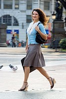 Spain, Barcelona, businesswoman walking in city plaza, side view, smiling, portrait blurred motion