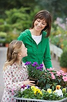 Mother and daughter 7-9 shopping for flowers in garden centre, girl holding pot plant, smiling