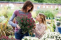Mother and daughter 7-9 shopping for flowers in garden centre, woman holding pot plant, smiling