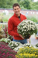 Man in red top shopping for flowers in garden centre, holding pot plant, smiling, portrait