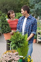 Couple shopping in garden centre, woman carrying pot plant, man pushing trolley, smiling