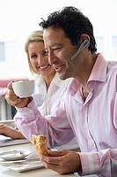 Man with mobile phone hands-free device, holding coffee and croissant, woman watching, smiling