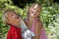 Blonde boy 6-8 and girl 7-9 playing with pet, dog licking boy's face, laughing, eyes closed