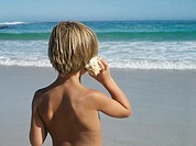 Blonde boy 5-7 standing on beach, listening to sea shell, looking at horizon over sea, rear view