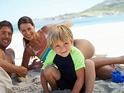 Two generation family sitting on beach, smiling, boy 5-7 crouching in foreground, portrait