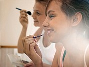 Two teenage girls 15-17 applying make-up in bathroom, smiling, close-up, profile lens flare (thumbnail)