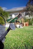 Watering can on garden lawn, house in background, focus on foreground