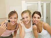 Three teenage girls 15-17 applying make-up in bathroom, smiling, front view, close-up