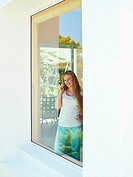 Teenage girl 15-17 looking through window at home, using mobile phone, smiling