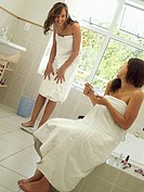 Teenage girl 15-17 in towel standing on bathroom scales, sister filing nails, smiling tilt