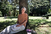 Mature man sitting in garden against tree, taking break from gardening, smiling, portrait