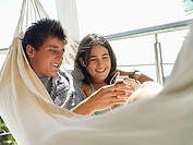 Teenage couple 15-17 relaxing in hammock on balcony, listening to MP3 player, smiling, close-up