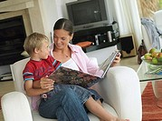 Mother and son 5-7 looking at photo album at home, boy in mother's lap in armchair, smiling tilt