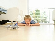 Blonde boy 5-7 playing with toy plane at home, lying on wooden floor, front view, surface level