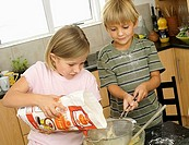 Boy 5-7 and girl 6-8 making cake mix in kitchen, girl pouring flour into glass bowl tilt