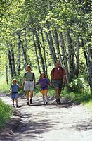 Parents with two daughters 4-5, 8-9 walking in forest