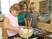 Mother and children 5-8 making cake mix in kitchen, boy holding sieve, girl dipping hand in bowl