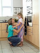 Mother and daughter 6-8 standing in kitchen, girl wearing striped apron, woman tying knot, smiling