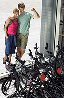 Young couple looking at new bikes in bicycle shop window display, elevated view