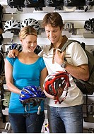 Young couple shopping for new cycling helmet in bicycle shop, smiling, display rack in background